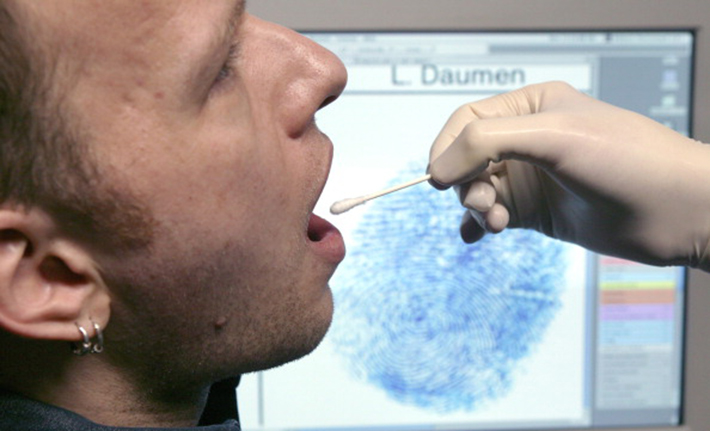 Taking a saliva probe for the determination of the genetic fingerprint, in the background a computerscreen showing a fingerprint (posed).